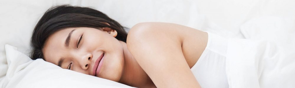 Portrait of beautiful young sexy asian woman with attractive smile enjoy fresh soft bedding linen mattress in white bed room modern apartment. Cute asia girl sleep resting, good night sleep banner